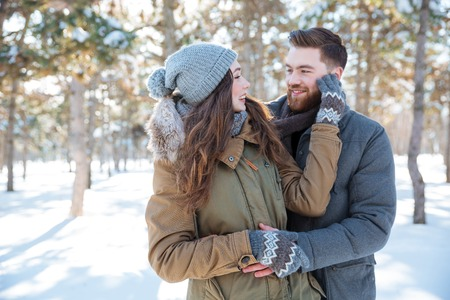 ragazza innamorata: Smiling young couple looking at each other in winter park