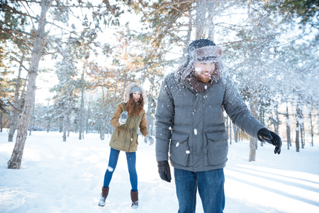 neve palle: Cheerful young woman playing snowballs with her boyfriend in winter park Archivio Fotografico