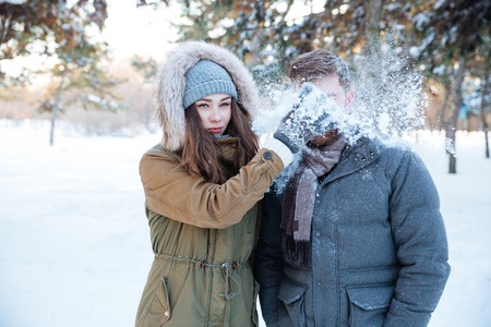 Amusing pretty young woman thowing snowball in her boyfriend face