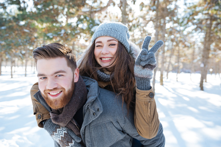 peace sign: Happy young couple walking in winter park and showing victory sign at camera