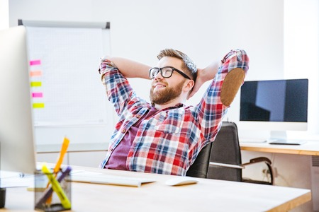 Happy handsome young man with beard sitting in the office with hands behind head and relaxing Stock Photo