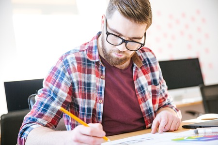 busy beard: Concentrated young man with beard in plaid shirt and glasses making sketches with pencil sitting at the table Stock Photo