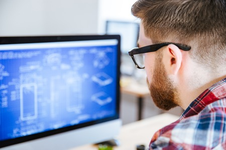 Close-up van de jonge mens in glazen met baard maken blauwdrukken op computer