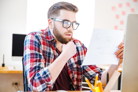 designer at work: Serious handsome man with beard in glasses sitting and looking at blueprint in office Stock Photo