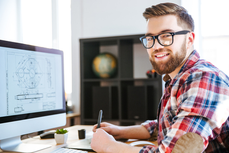 stylus: Portrait of happy handsome modern designer drawing blueprint on computer using pen tablet with stylus Stock Photo