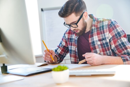 informal clothing: Handsome concentrated young man with beard working with blueprint using ruler and pencil in office Stock Photo