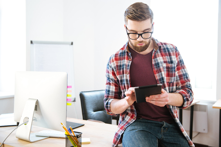 busy beard: Concentrated thoughtful young man with beard in glasses sitting on the table in office and using tablet Stock Photo