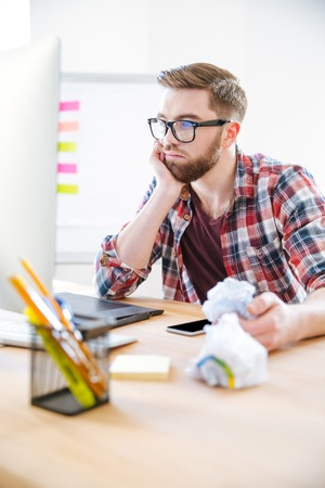 truthful: Thoughtful young man with beard in plaid shirt working and crumpling paper in the office