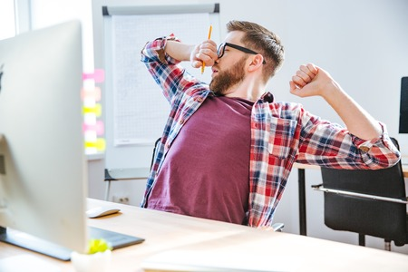 informal clothing: Tired handsome young man with beard in glasses stretching and yawning on workplace