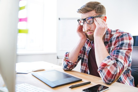 violence in the workplace: Tired exhausted young man with beard in glasses sitting on workplace and touching temples Stock Photo