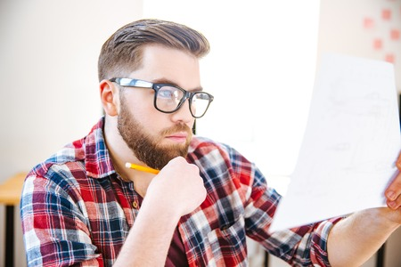 examined: Closeup of concentrated attractive young man in plaid shirt and glasses sitting on workplace and examined blueprint