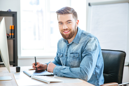 artist: Portrait of happy attractive young designer in jeans shirt working using pen tablet with stylus in office