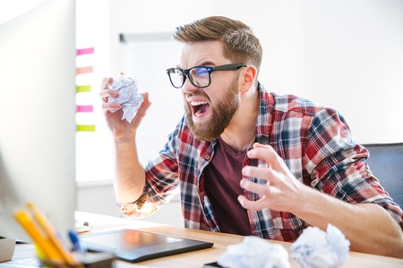 Angry crazy modern designer in glasses with beard yelling and crumpling paper on his workplace