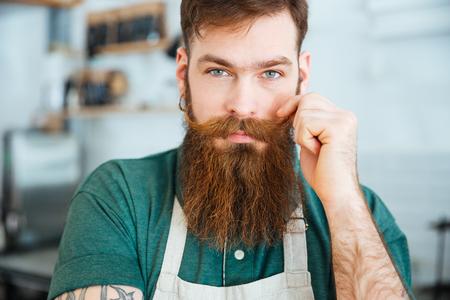 mandil: Primer retrato de hombre joven y guapo con barba en delantal blanco tocando el bigote