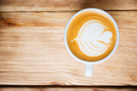 Top view of a cup with cappucino on the wooden table Stock Photo