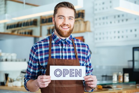 food shop: Happy attactive young barista in plaid shirt and brown apron holding open sign at the coffee shop Stock Photo