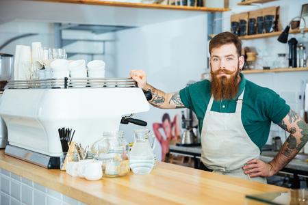 Retrato de guapo barista con la barba y el tatuaje en la mano de pie cerca de la máquina de café en la cafetería