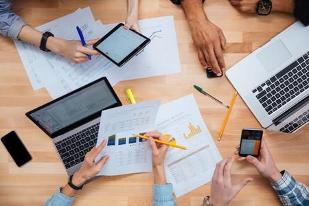 Grupo de personas que trabajan con ordenadores portátiles, tabletas y teléfonos inteligentes juntos y hacer el informe financiero