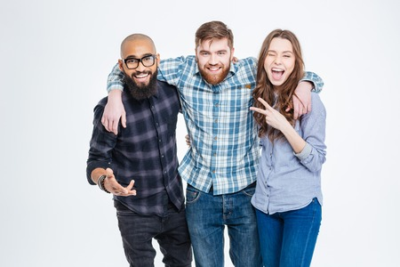 calvo: Feliz grupo de tres amigos en la ropa de sport de pie y riendo