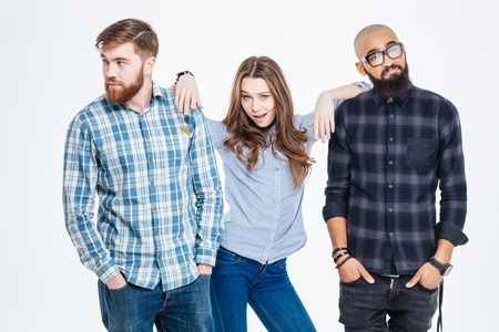 Beautiful confident young woman standing between two bearded pensive young men