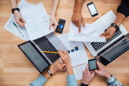 people working: Team of colleagues working for financial report using laptops and smartphones Stock Photo