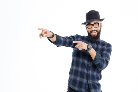 looking away from camera: Cheerful young african man with beard in black hat and glasses pointing away with both hands