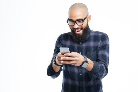 Glückliche afrikanische amerikanische unbehaarte Mann mit Bart lächelnd und mit Handy