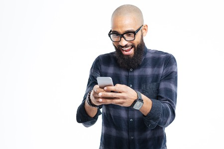 Happy african american hairless man with beard smiling and using mobile phone