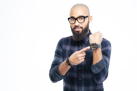Hairless attractive african young man in glasses with beard pointing on watch Foto de archivo