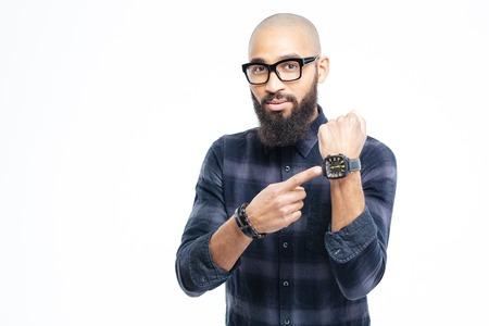 Jeune homme africain attrayant sans poils dans des verres avec la barbe pointant sur la montre