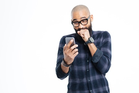 Cheerful bearded young african american bald man with beard in glasses using smartphone and laughing