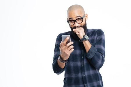 riendo: Hombre alegre con barba afroamericano joven calvo con barba en gafas con smartphone y riendo