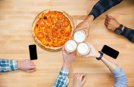lady on phone: Top view of group of friends eating pizza and drinking beer