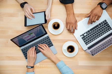 usando computadora: Vista superior del grupo multiétnico de jóvenes que utilizan ordenadores portátiles y tablet y el consumo de café