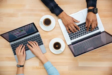 나무 테이블에 두 개의 노트북에 흑인 남자와 백인 여자 입력하는 손의 상위 뷰와 커피를 마시는