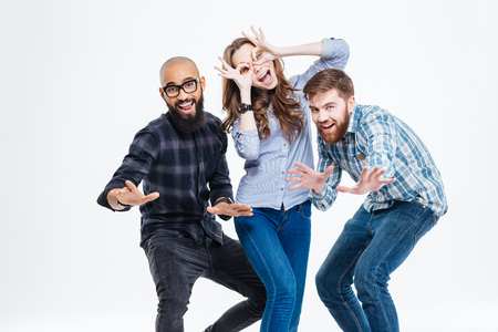 three persons: Group of students in casual clothes laughing and having fun Stock Photo