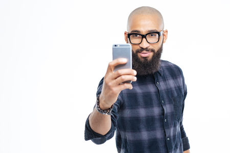 hairless: Handsome young hairless african young man with beard taking selfie using smartphone