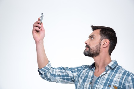 man searching: Casual man searching connection on the phone or making selfie photo on smartphone isolated on a white background