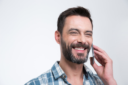 spontaneous expression: Happy man talking on the phone isolated on a white background