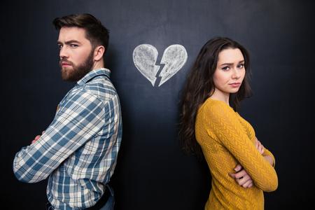 enojo: infeliz joven pareja de pie con los brazos cruzados sobre el fondo de la pizarra con dibujado corazón roto