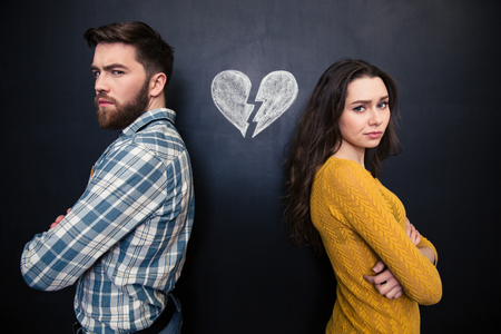 Unglückliche junge Paare stehend mit gekreuzten Armen über Tafel Hintergrund mit gebrochenen Herzen gezeichnet