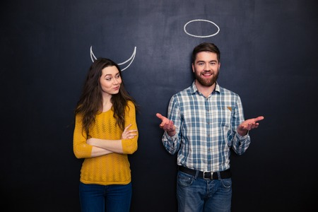 Happy young couple playing roles of devil and angel standing over blackboard background Фото со стока