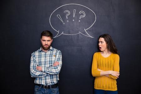 pareja enojada: Con el ceño fruncido joven pareja ofendida de pie con los brazos cruzados tras una discusión sobre el fondo pizarra