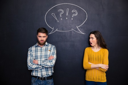 arm of a man: Frowning offended young couple standing with arms crossed after argument over chalkboard background Stock Photo