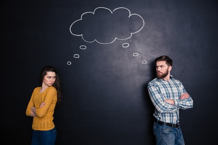 Frowning angry young couple standing with hands folded and thinking identically over background of chalkboard