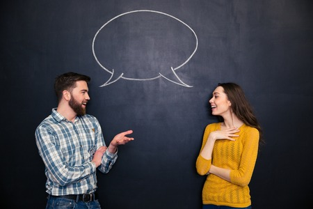 parejas de amor: feliz pareja de jóvenes hablando sobre fondo pizarra con extrae el diálogo vacío Foto de archivo