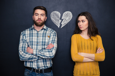 broken arm: Portrait of young couple after argument standing separately with hands folded over blackboard background Stock Photo