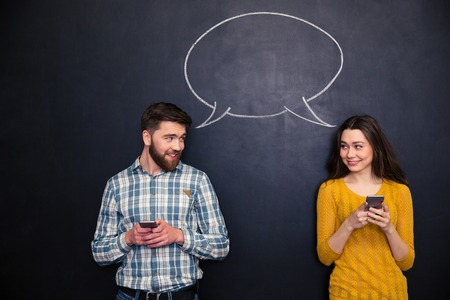 Beautiful couple using smartphones and flirting over blackboard background with drawn speech dialogue