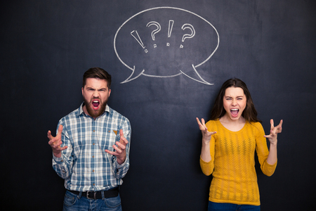Crazy young couple standing and screaming over chalkboard background Stock Photo