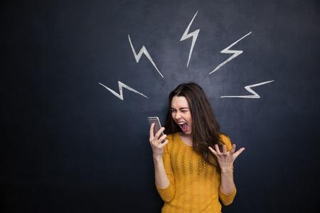 Pazzo giovane donna utilizzando smartphone e urla fuori bordo nero con lampi disegnate dietro di lei Archivio Fotografico